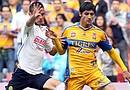 El centrocampista Paul Aguilar (i) de América lucha por el balón con Alan Pulido (d) de Tigres