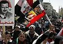 Varios sirios y palestinos ondean banderas y muestran fotos del presidente sirio Bachar al Asad mientras gritan eslóganes contra Israel, durante una manifestación convocada en la plaza Sabe Bahrat de Damasco, Siria