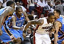 Mario Chalmers (2-d), jugador de los Heat, es marcado por Kendrick Perkins (i), Kevin Durant (2-i) y Thabo Sefolosha (d), de los Thunder, durante el cuarto partido de la final de la NBA, en el American Airlines Arena de Miami, Florida (EE.UU.)