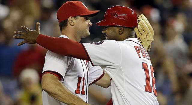 El coach de tercera base de los Nationals, Bo Porter, celebra con Ryan Zimmerman (11), al concluir el partido ante los Dodgers que dio el pase a los capitalinos a la postemporada de la Liga Nacional, el 20 de septiembre.