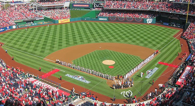 Los jugadores de los Washington Nationals y los Cardenales de San Luis formados en el terreno de juego en el Nationals Park que registra un lleno monumental, el miércoles 10.