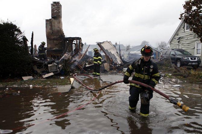 Un bombero lucha contra el agua en Linderhurst, Nueva York. AP