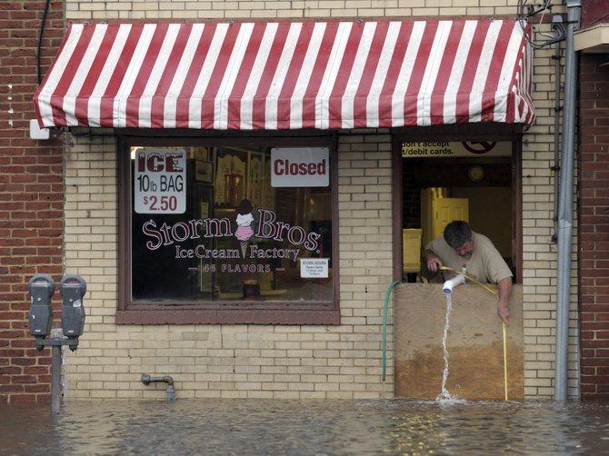 Sveinn Storm, dueño de una heladería en Annapolis, Maryland, saca agua de su negocio tras el paso de Sandy. AP