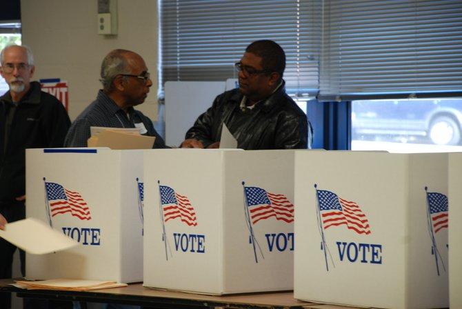 El oficial electoral Luis Marrero (izq.) ayuda a Evaristo Rosales, recién naturalizado, en su primera votación el martes 6. Crédito: ETL