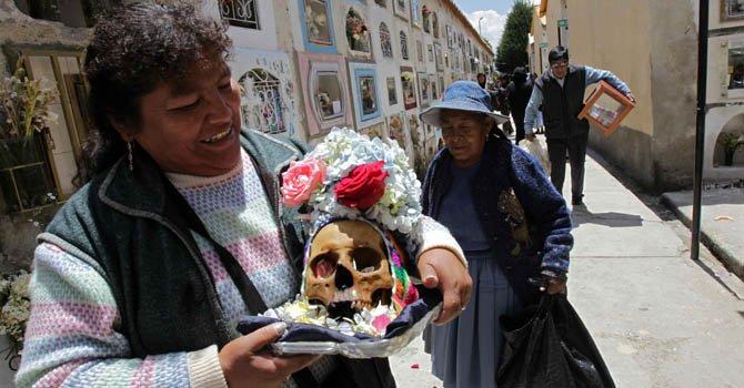 """Una mujer participa en una ceremonia durante los ritos de veneración a las calaveras en la llamada fiesta de las """"Ñatitas"""" en un cementerio de La Paz, Bolivia"""