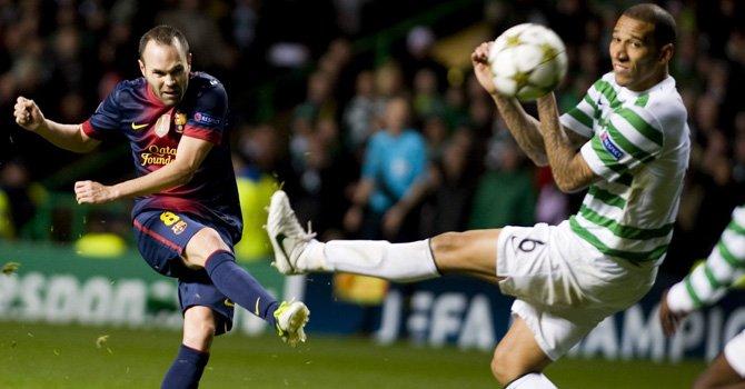 El centrocampista del FC Barcelona, Andrés Iniesta (izq), conecta el balón  ante Kelvin Wilson, del Celtic, durante el partido del grupo G de la Liga de Campeones en el Celtic Park de Glasgow, el miércoles 7.