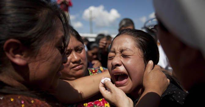 Una mujer llora durante el funeral de 10 miembros de una misma familia, víctimas del sismo que golpeó a Guatemala.