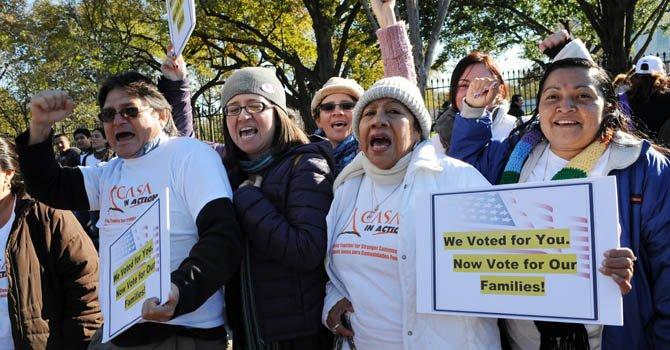 """Activistas e inmigrantes muestran carteles que dicen """"Hemos votado por tí, ahora vota por nuestras familias"""" y gritan consignas durante una manifestación ante la Casa Blanca."""