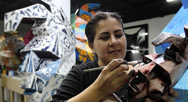 Una mujer pinta en un taller de Tonala, una de las 200 esculturas de fibra de vidrio con la forma del rostro del emperador maya Pakal.