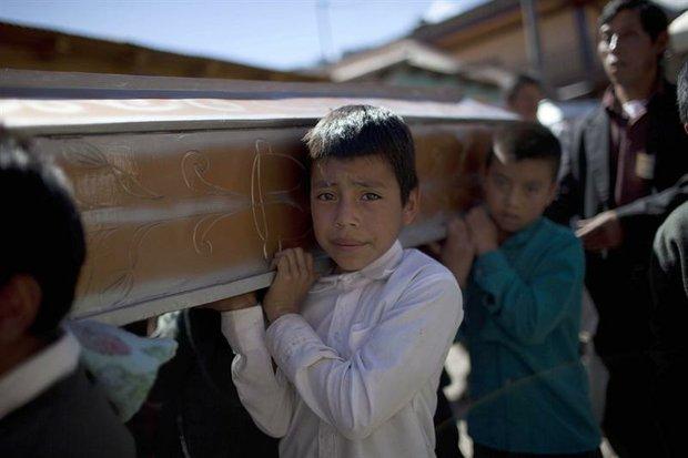 Varios niños cargan un ataúd el viernes 9 de noviembre, durante el funeral de 10 miembros de una misma familia, víctimas del sismo.
