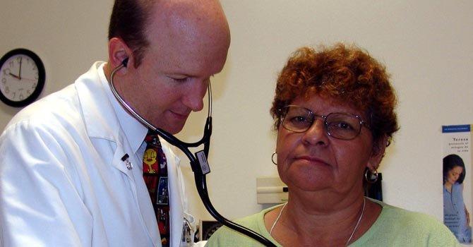 El doctor Paul Giboney, de la clínica Oscar Romero, ausculta a la paciente Ana Lizana.
