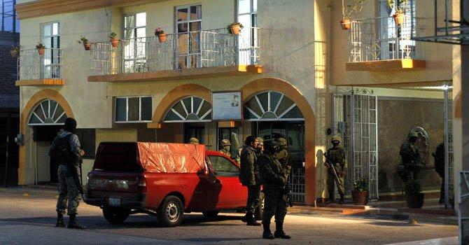 Soldados resguardan un domicilio después de un enfrentamiento armado.