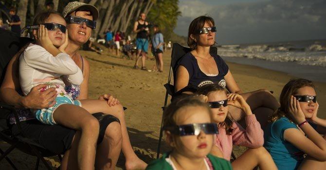 Familias observan el eclipse de sol sentados en una playa de Queensland, en Australia.