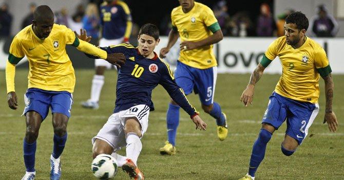 El colombiano James Rodríguez disputa el balón con los brasileños Ramires (izq.) y Daniel Alves durante el amistoso entre Brasil y Colombia en East Rutherford, NJ, el 14.