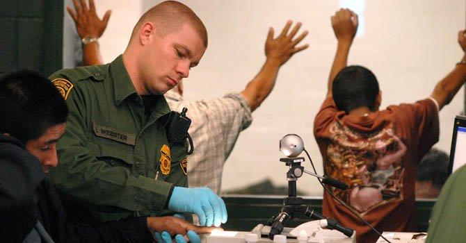 Un agente de la Patrulla Fronteriza de EE.UU tomando las huellas digitales de un detenido.