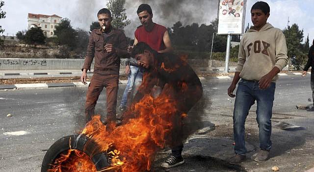 Varios palestinos prenden fuego a un neumático mientras participan en una manifestación contra Israel y en apoyo a los palestinos de la franja de Gaza, lunes 19 de noviembre de 2012.