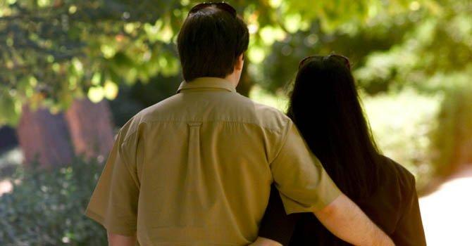 Una pareja pasea por un parque.