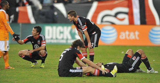 El brasileño Maicon Santos (der.), yace en la cancha del RFK al lado de sus compañeros del D.C. United, Perry Kitchen, Dejan Jakovic y Lewis Neal, el domingo 18 de noviembre.