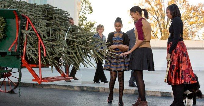 La primera dama Michelle Obama, sus hijas Sasha y Malia, y su perro Bo reciben el árbol de Navidad el viernes 23 de noviembre en la Casa Blanca.