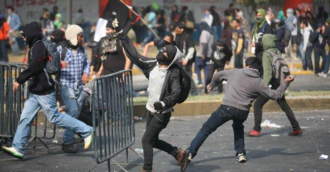 Jóvenes activistas se enfrentan a policías federales el sábado 1 de diciembre, en las inmediaciones de Palacio Legislativo de Ciudad de México, horas antes de la investidura del nuevo presidente del país, Enrique Peña Nieto.