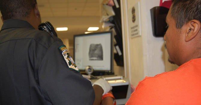 Un oficial verifica el estatus migratorio de un detenido a través del programa federal 287g.
