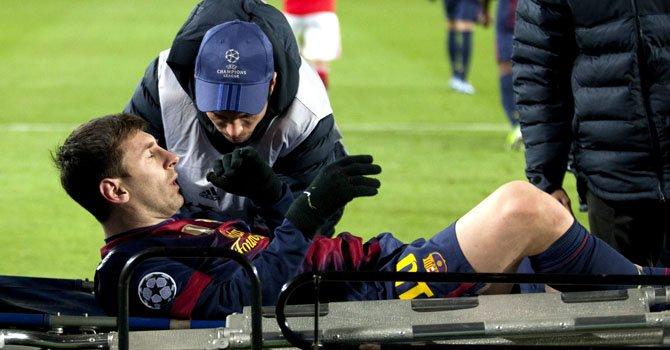 El delantero argentino del FC Barcelona, Lionel Messi, al salir en camilla del partido de su club ante el Paris Saint Germain en la Champions League.