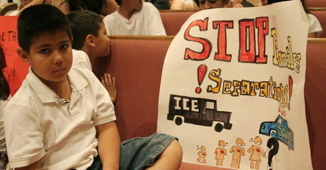 El niño Diego Andrade muestra un cartel que dibujó donde defiende la importancia del problema migratorio.