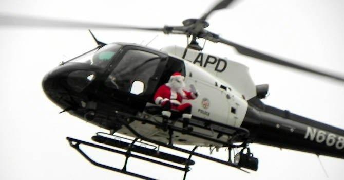 Santa Claus reparte en helicóptero regalos a niños