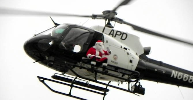 Santa Claus saluda a la gente desde un helicóptero cerca del Hospital Ortopédico de Los Ángeles (LAOH) a donde llega para entregar regalos a niños necesitados.