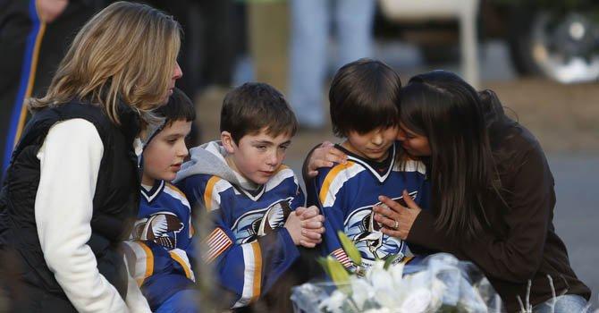 De izq. a der. Jean Bradley, Steven Turchetta, de 9 años, Matthew Bradley, de 9, Ashton Baltes, de 10, y su madre  Elonda Baltes frente a un altar de las víctimas, incluidos 20 niños, que murieron en la Sandy Hook Elementary School, Saturday en Connecticut.