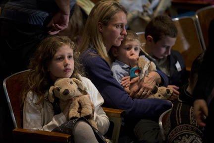 Una madre con sus hijos en la vigilia en donde habló el presidente Barack Obama el domingo 16 de diciembre.