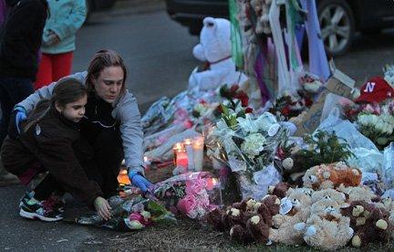 Una madre lleva flores a un altar improvisado en Newtown, Connecticut en memoria de las 26 personas que perdieron la vida en una masacre.