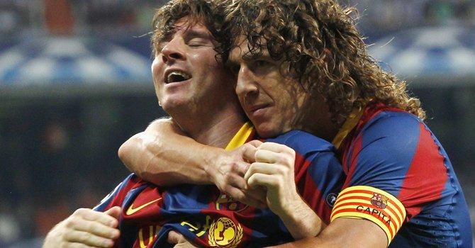 El defensa español Carles Puyol (der.) del Barcelona abraza a su compañero Lionel Messi. Puyol anunció el martes 4 de marzo que dejará al club a finales de esta temporada.