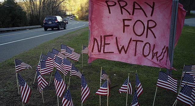 """Banderas y un cartel en el que se lee """"oren por Newtown"""" permanece en una colina en dirección a esa localidad de Connecticut."""