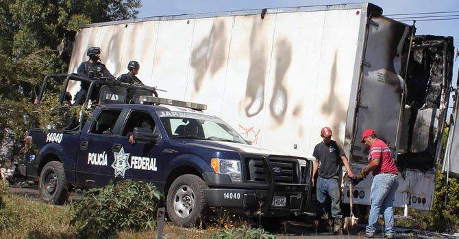Policías federales custodian mientras expertos forenses revisan vehículos quemados este domingo 23 de diciembre , en una carretera de Michoacán, México.