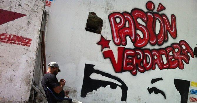 Un hombre sentado frente a un grafiti de apoyo al presidente venezolano, Hugo Chávez, en Caracas.