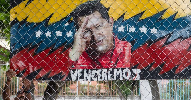 Un hombre cuelga un cartel alegórico al presidente de Venezuela, Hugo Chávez, el miércoles 2 de enero, en Caracas, Venezuela