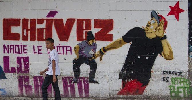 Un joven camina frente a una pared pintada con referencias al presidente Venezolano Hugo Chávez el lunes 7 de enero en Caracas, Venezuela.