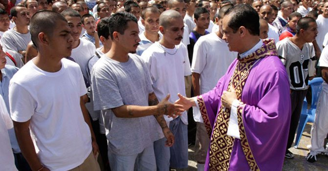 Monseñor Fabio Colindres estrecha la mano de pandilleros en San Salvador, El Salvador. Colindres ha jugado un papel clave entre la tregua de pandillas.