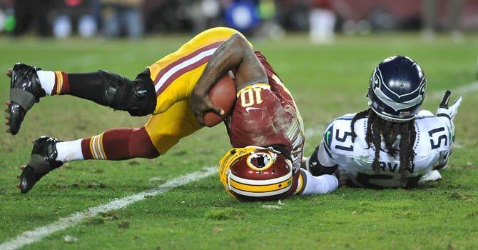 El mariscal de campo de los Washington Redskins, Robert Griffin III (izq.), al momento de lesionarse en el partido de su equipo contra Seattle el domingo 6 de enero en FedExfield de Landover, MD.