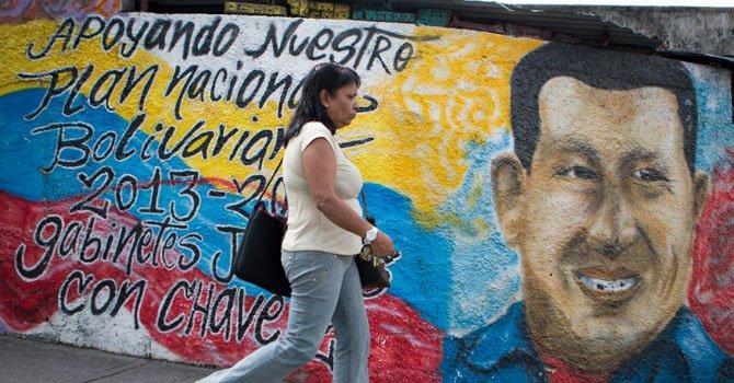 Una mujer camina frente a una pared con mensajes en apoyo al presidente venezolano Hugo Chávez el miércoles 9 de enero en Caracas, Venezuela.