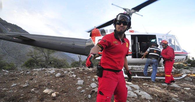 Federales y de protección civil observando el sitio donde cayó el avión privado en el perdieron la vida la cantante  Jenni Rivera el 9 de diciembre.