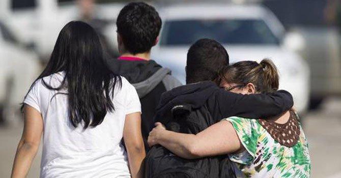Una mujer abraza a un grupo de estudiantes que fueron evacuados del campus de Houston de la Universidad Lone Star en donde hubo una balacera que dejó a tres heridos.
