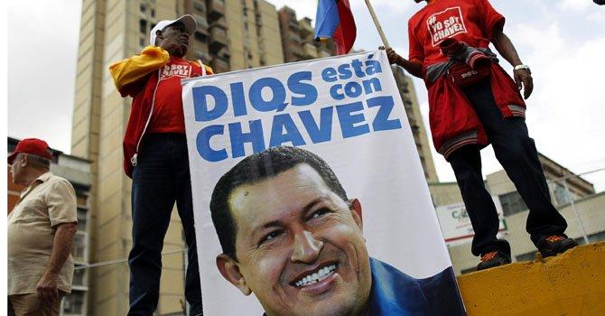 Dos hombres sostienen un cartel con una imagen del presidente venezolano Hugo Chávez el miércoles 23  durante una marcha en Caracas, Venezuela.