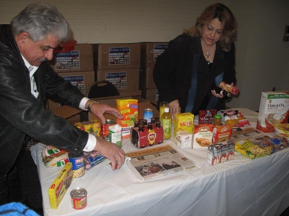 Ramón Pagan, de EMD SALES, y su esposa Mireya, organizan los alimentos en la entrega de Bolsas de Amor, el sábado 26.