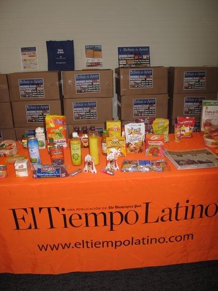 En la mesa, se mostraron los productos de EMD SALES, algunos de los cuales formaron parte de las cajas entregadas. Atrás, las cajas esperan por las familias.