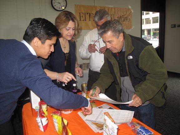Gilberto Aguilar (der.) firma el comprobante de que recibió la suculenta caja de alimentos.