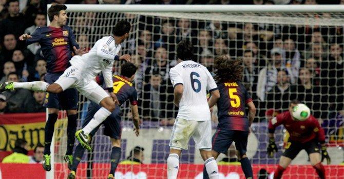 El defensa francés del Real Madrid, Raphael Varane (2do. izq.), remata de cabeza ante la defensa del F. C. Barcelona, consiguiendo el primer gol del equipo blanco, durante el encuentro en el estadio Santiago Bernabéu, el 30.