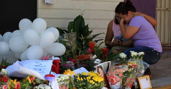 Dos mujeres lloran junto un altar con flores y fotografías en honor a las víctimas frente a la discoteca Kiss el martes 29 de enero donde un incendio dejó a más de 200 muertos y 143 heridos en Santa María, Brasil.