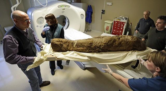 Los técnicos Marion Price (der.) y Tesha Reid (frente) y el curador del Museo de Virginia de Bellas Artes, Tim Harriss (izq.) junto con la conservadora de objetos Kathy Gillis preparan, el 1 de febrero, a una momia egipcia de 4.000 años para meterla al tomógrafo del centro HCA Virginia en Richmond.